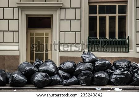 Pile of black plastic trash bags on sidewalk - stock photo