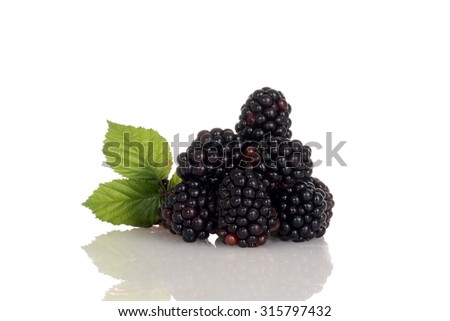 pile of blackberries with leaves - stock photo