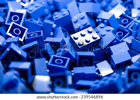 Pile of blue color building blocks with selective focus and highlight on one particular block using available light. - stock photo