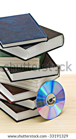 Pile of books  and DVD disk as symbols of old and new methods of information storage - stock photo