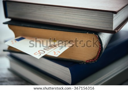 Pile of books and euro bills - stock photo