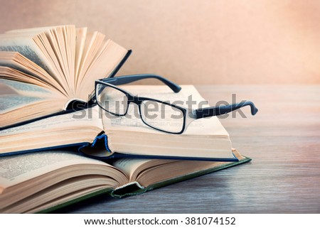 Pile of books and eyeglasses on it on wooden table, close up - stock photo