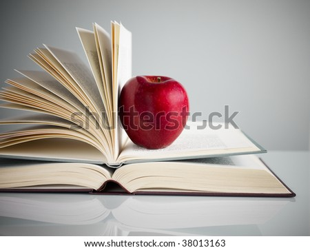 pile of books and red apple on desk. Copy space - stock photo