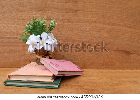 pile of books and vase on wooden background