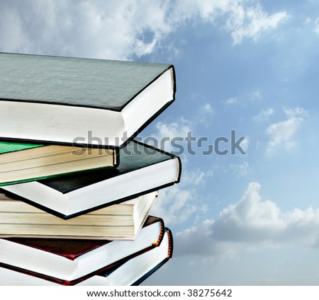 Pile of books on sky background