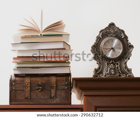 Pile of books standing on an old trunk, next to the antique clock. - stock photo