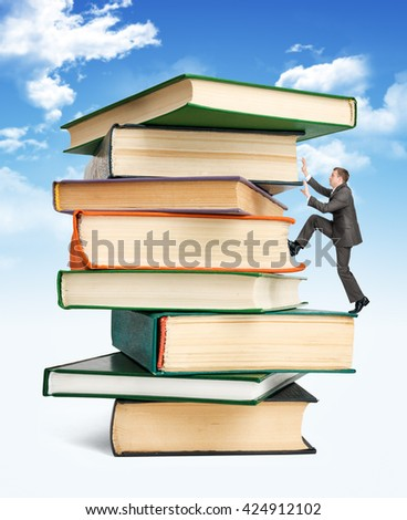 Pile of books with businessman climbing it on blue sky background - stock photo