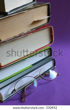 pile of books with reading glasses