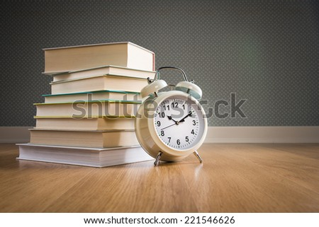 Pile of books with vintage alarm clock on parquet wooden floor, back to school concept. - stock photo