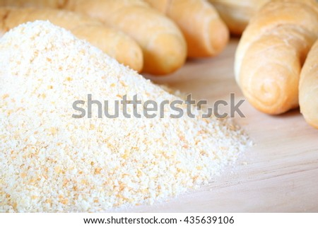 Pile of breadcrumbs and blurry bread rolls in the background - stock photo