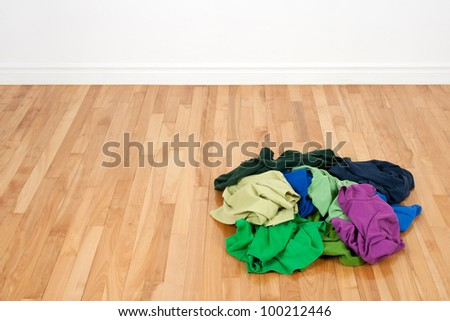 Pile of bright colorful clothes on the wooden floor in empty room. - stock photo