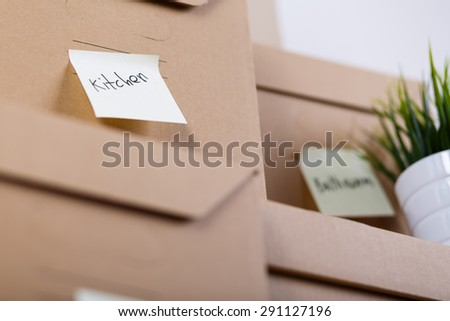 Pile of brown cardboard boxes with house or office goods. Different stuff packed in carton boxes. Moving concept. Set of cargo boxes with yellow sticker labels ready for transportation and unpacking - stock photo