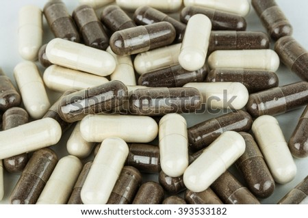 Pile of brown herbal and white capsules - stock photo