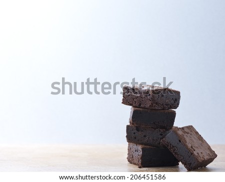Pile of brownies on wooden table - stock photo