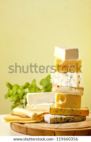 Pile of cheese many various types on cutting board - stock photo