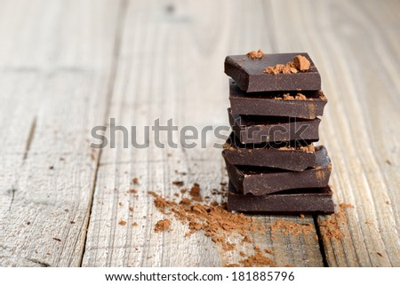 Pile of chocolate pieces with cocoa on wooden background - stock photo