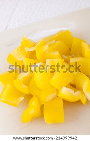 Pile of Chopped Yellow Pepper on White Cutting Board - stock photo