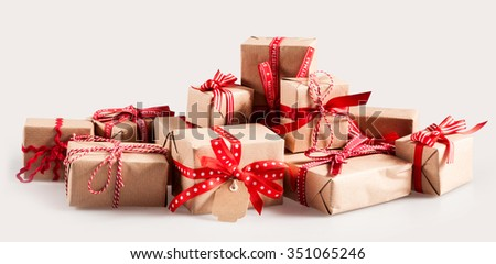 Pile of Christmas gifts with colorful red bows wrapped in brown paper with gift tags to celebrate a family Xmas over a white background