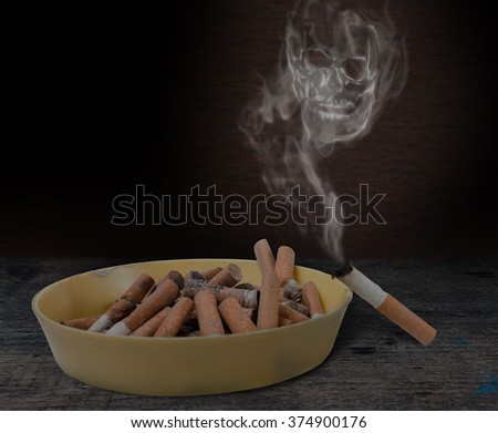 Pile of cigarette butts in the ashtray and the skull of the smoke. Quit smoking now - stock photo
