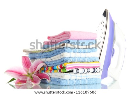 Pile of clothes with lily and electric iron, isolated on white - stock photo