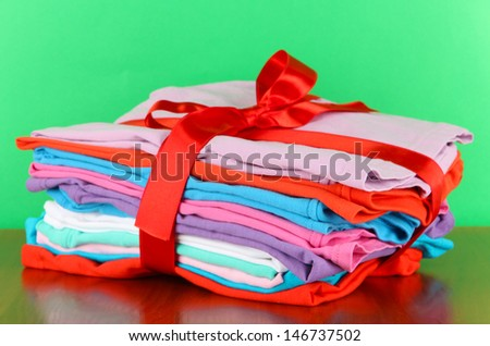 Pile of clothing with red ribbon and bow on table on green background - stock photo