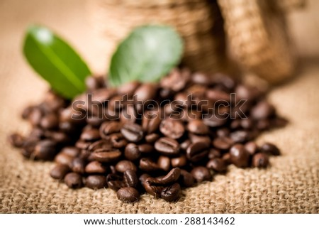 pile of coffee beans and wooden spoon in jar - stock photo