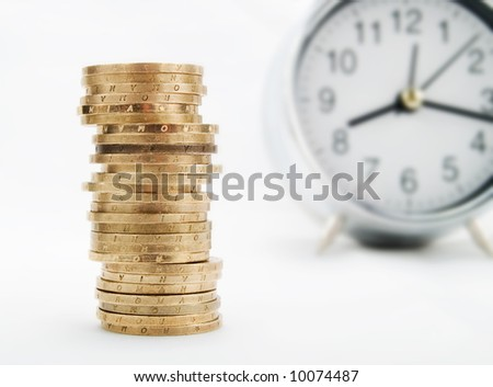 Pile of coins and alarm clock on a white background - stock photo