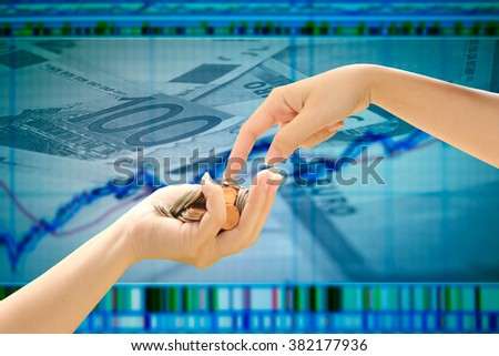 pile of coins in hand with blur image of graph stock market