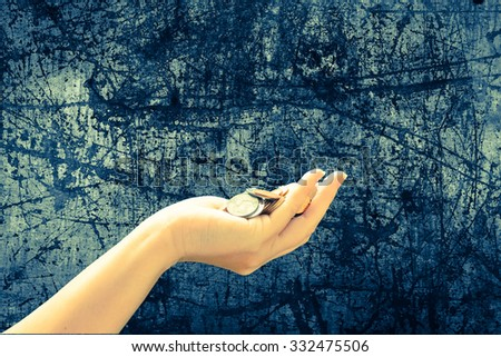 pile of coins in hand with scratched steel plate background ,vintage tone