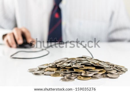 Pile of coins with hand on computer mouse, businessman can manage personal finance directly and promptly - stock photo