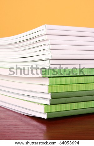 Pile of color magazines isolated on yellow background - stock photo