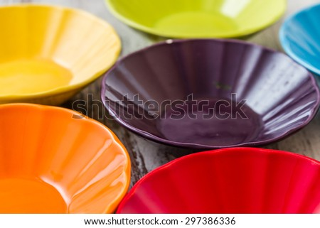 Pile of colorful ceramic bowls over white wooden background