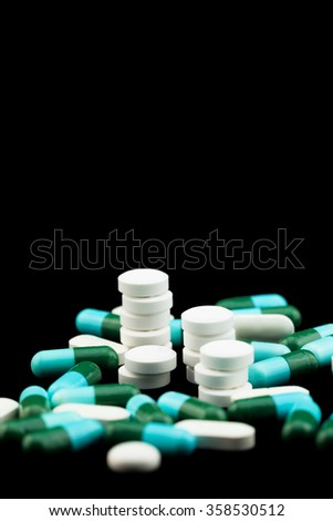 Pile of colorful drugs pills capsules for health care industry in black background