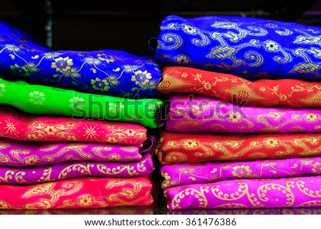 Pile of colorful fabrics on shelves in a shop - stock photo