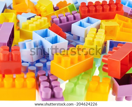 Pile of colorful plastic toy construction bricks as a background composition