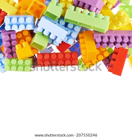Pile of colorful plastic toy construction bricks isolated over the white as a copyspace background composition - stock photo