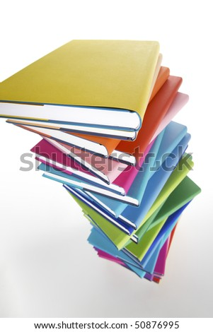 Pile of colorful real books on white background, side view.