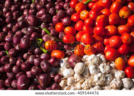 Pile of colourful fresh red Roma tomatoes, purple Spanish onions and white garlic at an outdoor vegetable market in Thimphu, Bhutan. - stock photo