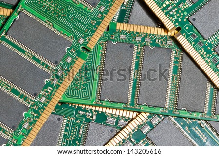 pile of computer memory chips on green printed circuit boards