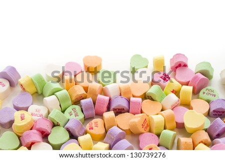 Pile of conversation heart candies on white background. - stock photo