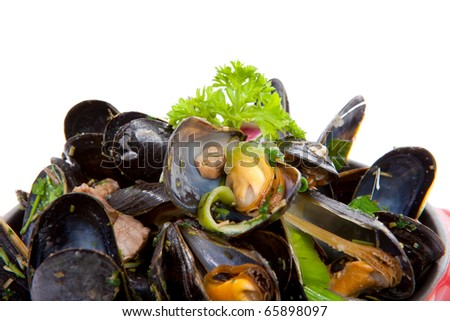 pile of cooked mussels in red casserole over white background