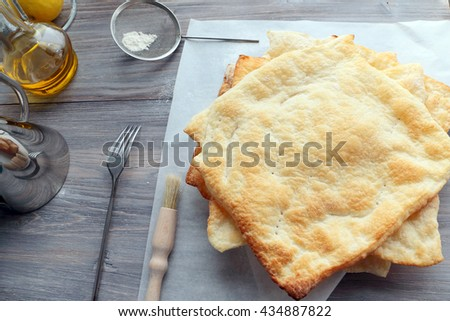 Pile of cooked pie layers on a table ready for next operation - stock photo