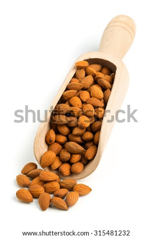 Pile of cracked and shelled almond kernels in wooden scoop on white background - stock photo