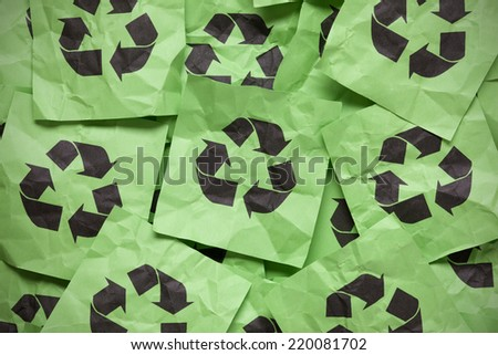 Pile of crumpled green paper notes with Recycling symbols. - stock photo