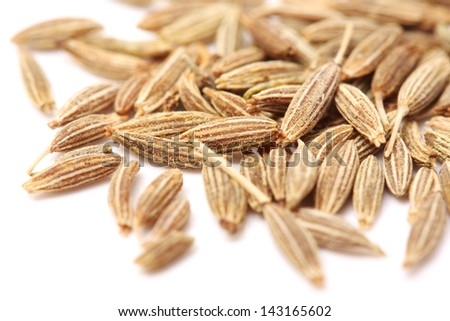 Pile of cumin seeds captured from above isolated on white - stock photo