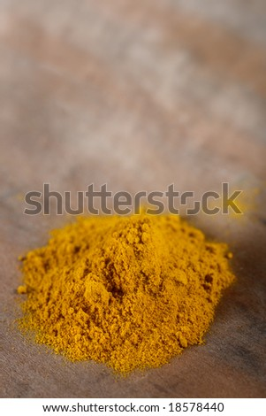 pile of Curry powder on old wooden background, shallow DOF - stock photo