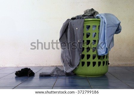 Pile of dirty clothes in a washing basket / Pile of dirty clothes - stock photo