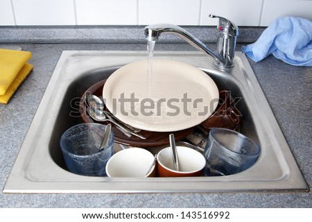 pile of dirty dishes in kitchen sink with running water - stock photo