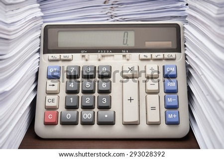 Pile of documents on desk stack up high with calculator on office desk - stock photo
