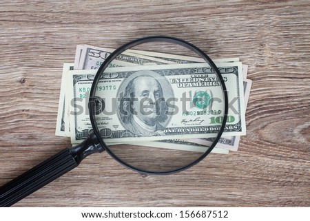 pile of 100 dollars  banknotes under looking glass - stock photo